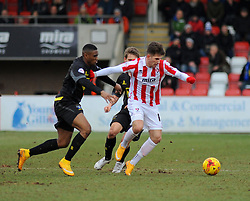 Cheltenham Town's Zack Kotwica challenges Bury's Kelvin Etuhu for possession- Photo mandatory by-line: Nizaam Jones - Mobile: 07966 386802 - 14/02/2015 - SPORT - Football - Cheltenham - Whaddon Road - Cheltenham Town v Bury - Sky Bet League Two