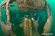 divers explore stern cabin of the wreck known as the Japanese Patrol Boat, a 32 m long trawler-style WW II Japanese vessel, possibly a tugboat or submarine chaser, sunk upright in 18-25m of water in Triboa Bay, within Subic Bay, Philippines, presumed to have been sunk by an Allied air attack in 1944-1945; MR 378, 379