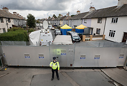 © Licensed to London News Pictures. 18/09/2017. London, UK. A policeman stands at a barrier outside the house (R) in Sunbury, west London, where detectives investigating the Parsons Green tube bombing are continuing to search for clues. Investigations are continuing into the failed bombing of an underground train at Parsons Green station on September 15, 2017. Detectives have searched three properties and have two people in custody. Photo credit: Peter Macdiarmid/LNP