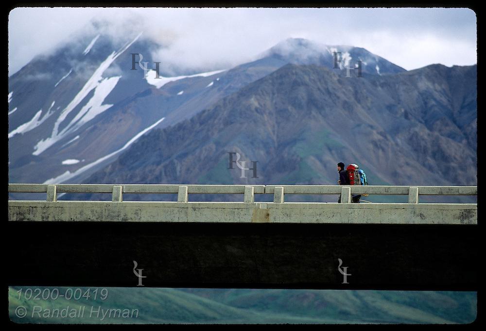 Backpackers cross Savage River bridge against backdrop of cloudy Alaska Range; Denali National Park. Alaska