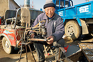 Chinese shoemaker cobbler making shoes with stitching machine and last in farming village of Hui Wen in Shandong Province China