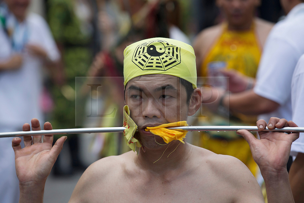 © Licensed to London News Pictures. 28/09/2014. Ipoh, Malaysia. A devotee with a rod pierce through his mouth walks along a street as devotees process with deities through the streets of central Ipoh, Malaysia on the 5th day of the Nine Emperor Gods Festival, Sunday, Sept. 28, 2014. The festival is a nine-day Taoist celebration to mark the birth of the Nine Emperor Gods from the first day to the ninth day of the ninth moon in Chinese Lunar Calender. The origin of the Nine Emperor Gods (stars of the Northern constellation) can be traced back to the Taoist worship of the Northern constellation during Qin and Han Dynasty and absorb this practice of worshipping the stars and began to deitify them as Gods. Photo credit : Sang Tan/LNP