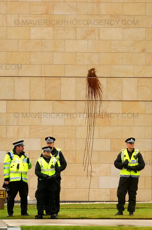 EDINBURGH, UK - 23rd August 2010: Climate change protesters staged a variety of protests across Edinburgh today during the 'Day of Action' after having set up camp close to the Royal Bank of Scotland headquarters in Edinburgh...The Camp for Climate Action is protesting about RBS's role in financing oil industry developments...Picture shows police officers stand by after protesters fired an oil like substance from a catapult at the RBS head quarters at Gogarburn...(Photograph: Richard Scott/MAVERICK)