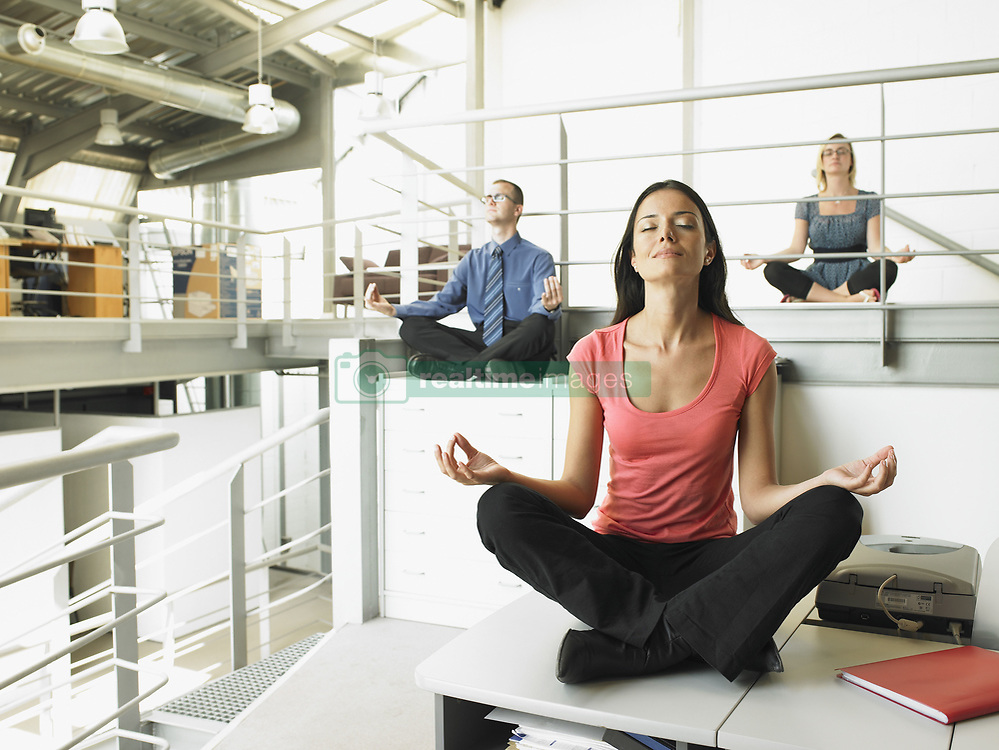 Oct. 07, 2006 - Young adults sitting on office desks in a yoga position. Model and Property Released (MR&PR) (Credit Image: © Cultura/ZUMAPRESS.com)