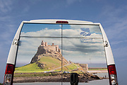 The rear of a National Trust membership van features Lindisfarne castle, on 27th September 2017, on Lindisfarne Island, Northumberland, England. The Holy Island of Lindisfarne, also known simply as Holy Island, is an island off the northeast coast of England. Holy Island has a recorded history from the 6th century AD; it was an important centre of Celtic and Anglo-saxon Christianity. After the Viking invasions and the Norman conquest of England, a priory was reestablished.