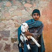 Boy with pet goat in village of Chandelao, Rajasthan