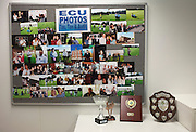 Work colleagues and friends' pictures and trophies displayed on a board in an auditing company's London headquarters