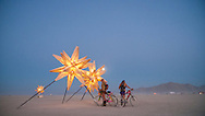 Burners on bikes pause at the star constellation art on the playa at dusk, Burning Man Festival