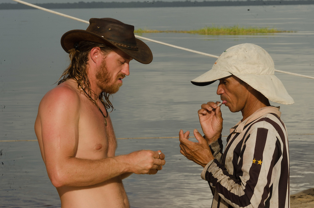 Negro river, stop at the beach of Praia Grande. Making tobacco cigarettes with a native.