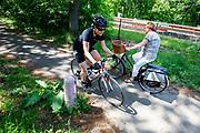 Een wielrenner en een vrouw op een stadsfiets ontwijken elkaar op een fietspad tussen Soest en Den Dolder door het bos.<br /> <br /> Cyclists ride a cycle path between Soest and Den Dolder in the woods.