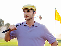 Young male golfer standing on course holding club on shoulder portrait