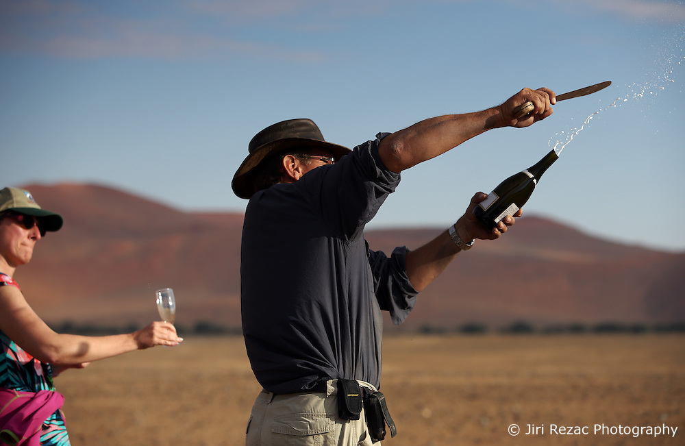 NAMIBIA SOSSUSVLEI 21APR14 - Balloon pilot Eric Hesemans decapitates a bottle of champagne after a flight with Namib Sky Balloon Safaris in Sossusvlei, Namib Desert, Namibia.<br /> <br /> jre/Photo by Jiri Rezac<br /> <br /> © Jiri Rezac 2014