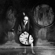 Black and white photo collage of a sad-looking woman holding a clock with her feet submerged in water and water pouring in through portholes in the background
