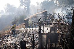October 28, 2019, Los Angeles, California, USA: Firefighters hose hot spots at a home destroyed by the Getty fire on Tigertail road Monday. The Getty Fire in Los Angeles erupted early Monday and is forcing thousands of residents to flee their homes as winds reach extremely dangerous levels in Southern California. (Credit Image: © David Crane/Orange County Register via ZUMA Wire)