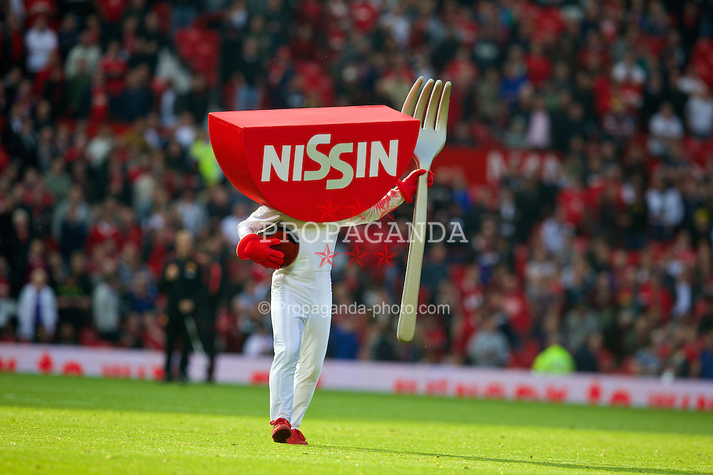 "MANCHESTER, ENGLAND - Sunday, September 14, 2014: A man dressed as a noodle packet, Nissin Manchester United's  ""official noodle partner"" dances on the pitch at half-time during the Premier League match against Queens Park Rangers at Old Trafford. (Pic by David Rawcliffe/Propaganda)"