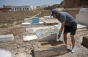 Tunisian Jew ,Yossef Sabbagh, a member of the Hevra Kadisha religious committee responsible for  burials ,as he stands by cracked marble tombstones that litter the outer perimeter of the cemetery behind the Great Synagogue of the tiny Tunisian Jewish community on the island of Djerba on May 27,2016. Vandals  did not break the gravestones but instead the graves were exhumed and sent to Israel for reburial ,said Sabbath. (Photo by Heidi Levine).