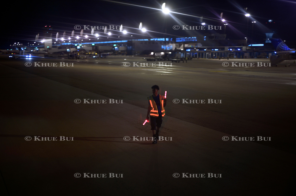 An airport employee guides a plane backing up from its gate July 15, 2018, at Dulles International Airport (IAD), VA.<br /> <br /> Photo by Khue Bui