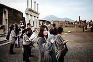 """Pompei, Napoli. Un gruppo di turisti asiatici nella piazza del foro, negli scavi archeologici di Pompei;  group of Asian tourists in the """"Foro"""" of archaeological site of Pompeii."""