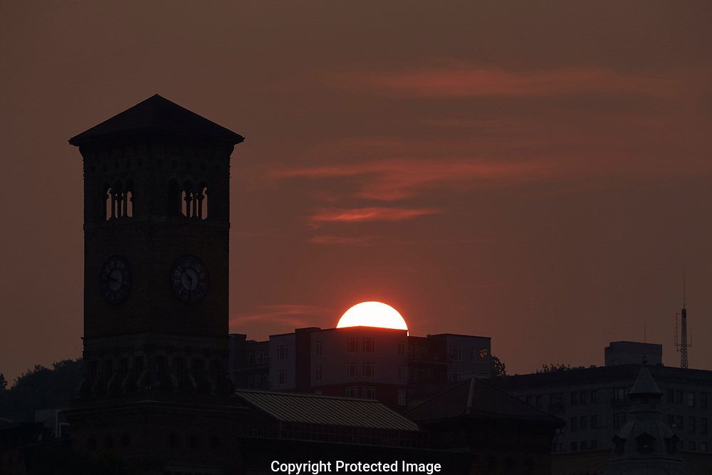 Red sun sets behind the former city hall building in Tacoma, WA, Monday, Aug. 7, 2017. The sun is red due to forest fire smoke drifting in from British Columbia. (Photo/John Froschauer)