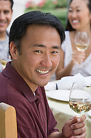 Man drinking wine with friends outdoors