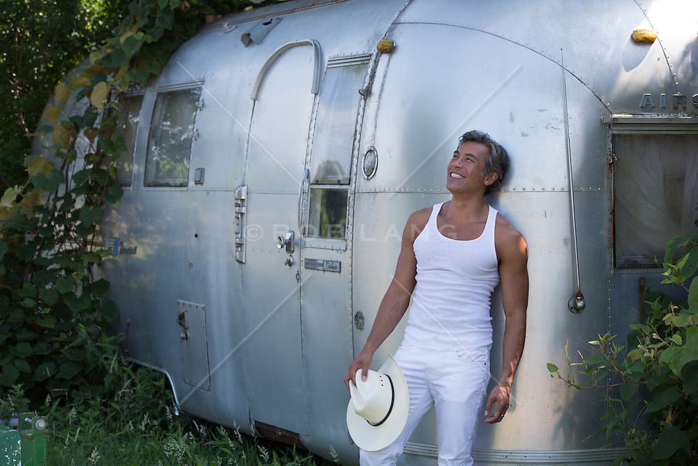 Asian American man smiling while leaning against an airstream