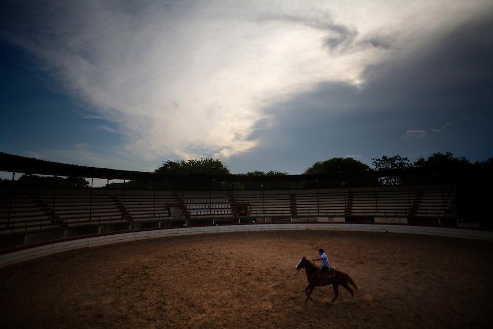 Julia Robinson photo.A charro warms up his horse in the arena at the San Antonio Charro Ranch.