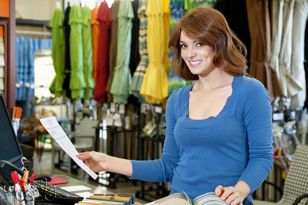 Portrait of beautiful young woman with paper and textile samples standing in store