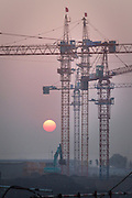 The sun sets amidst a cluster of cranes at the construction site of a housing development in Jinnan, in Tianjin Municipality.