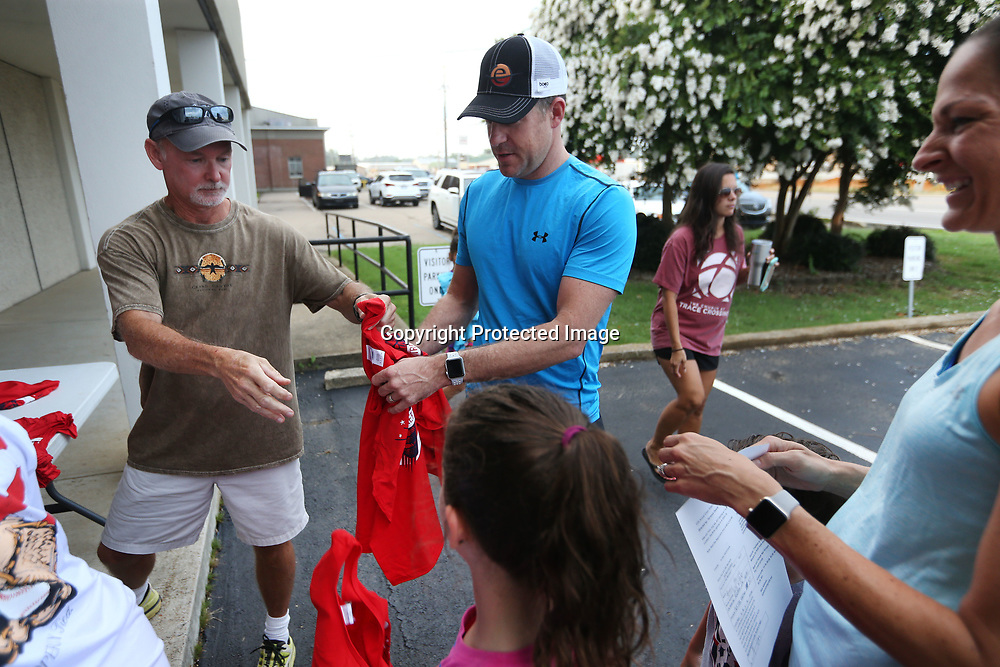 Richard Royce, a member of the Tupelo Running Club, hands out race shirts to David Horine, of Kokomo Indiana, his wife Annie, and their two children Laila, 8, and Greyson, 5, after they registered for the Green Street Mile Run Tuesday morning in Tupelo.