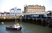 Fishing boat in harbour, Harwich, Essex with Pier Hotel and Former Great Eastern Hotel in background.