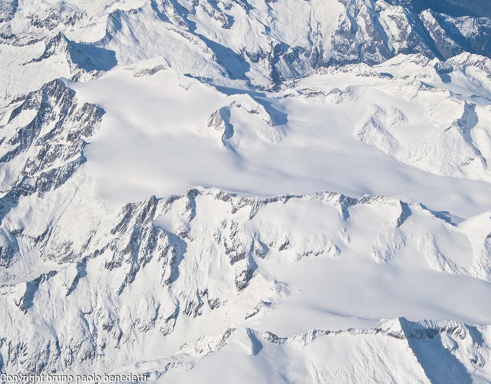 Aerial view of Alps. Fall season. Mountains peaks with valleys covered by snow and fog.