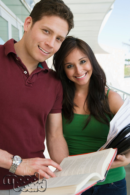 Two students holding books at school, smiling, portrait