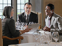 Three business people sitting at restaurant table woman holding documents