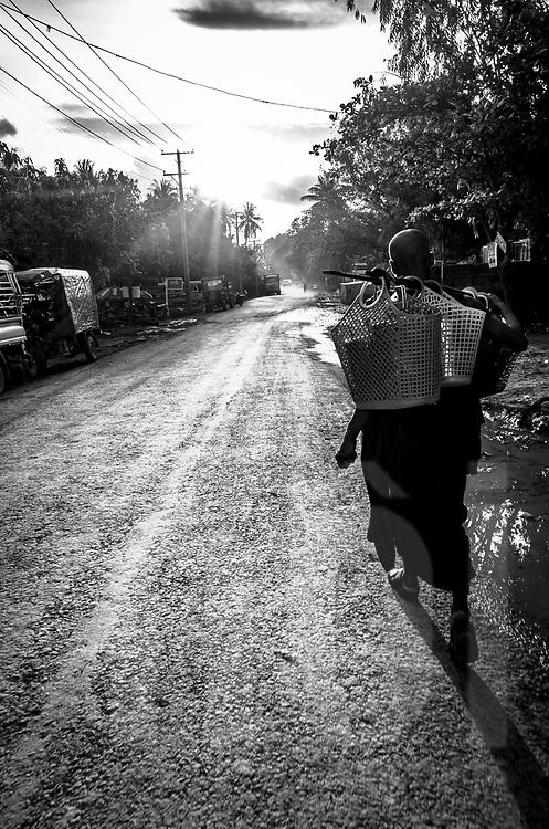Silhouette carries baskets along a road of Mrauk U, Rakhine State, Myanmar, Asia