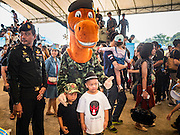 "14 JANUARY 2017 - BANGKOK, THAILAND: Children pose for pictures with the mascot of the 2nd Cavalry Division of the Royal Thai Army during Children's Day activities at the King's Guard, 2nd Cavalry Division base in Bangkok. Thailand National Children's Day is celebrated on the second Saturday in January. Known as ""Wan Dek"" in Thailand, Children's Day is celebrated to give children the opportunity to have fun and to create awareness about their significant role towards the development of the country. Many government offices open to tours and military bases hold special children's day events. It was established as a holiday in 1955.       PHOTO BY JACK KURTZ"