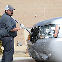 Justin Bailey scrubs the bugs off the front of a customers vehicle Saturday at Shine Time Superwash before they go through the actual carwash