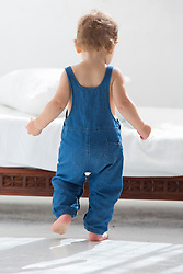Back view of Baby Boy Walking in Bedroom Wearing Dungarees