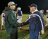 Cedar Rapids Kennedy head coach Tim Lewis shakes hands with Cedar Rapids Xavier head coach Duane Schulte after the Class 4A quarterfinal playoff game at Saints Field in Cedar Rapids on Friday, November 8, 2013.