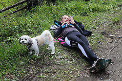 © Licensed to London News Pictures. 30/04/2016. Harewood, UK. A spectator lays next to his dog as he waits for the riders to ascend the climb in Harewood near Leeds in West Yorkshire during the second stage of the 2016 Tour De Yorkshire. The three-day road cycling race held annually across Yorkshire is in it's second year. Photo credit : Ian Hinchliffe/LNP