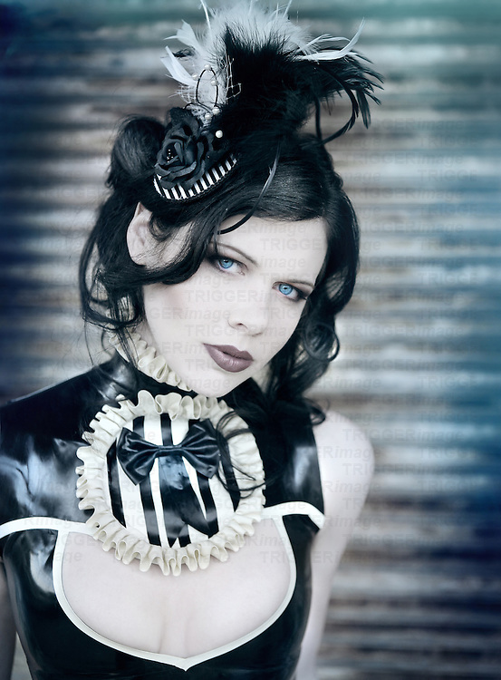 Close up of a pale gothic young woman wearing a black latex dress with bright blue eyes