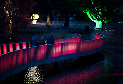 © Licensed to London News Pictures. 21/11/2017. London, UK. Visitors cross the Sackler Crossing at the opening of Christmas at Kew at Royal Botanical Gardens, Kew. The spectacular displays are illuminated by over one million tiny twinkling lights placed all over Kew Gardens - open Wednesdays – Sundays from 22 November 2017 – 2 January 2017. London, UK. Photo credit: Peter Macdiarmid/LNP