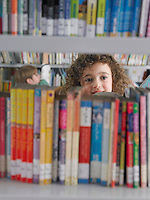 Girl selecting books from library bookshelf