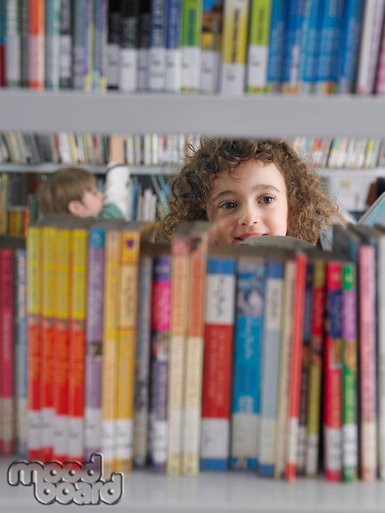 Girl selecting books from library bookshelf