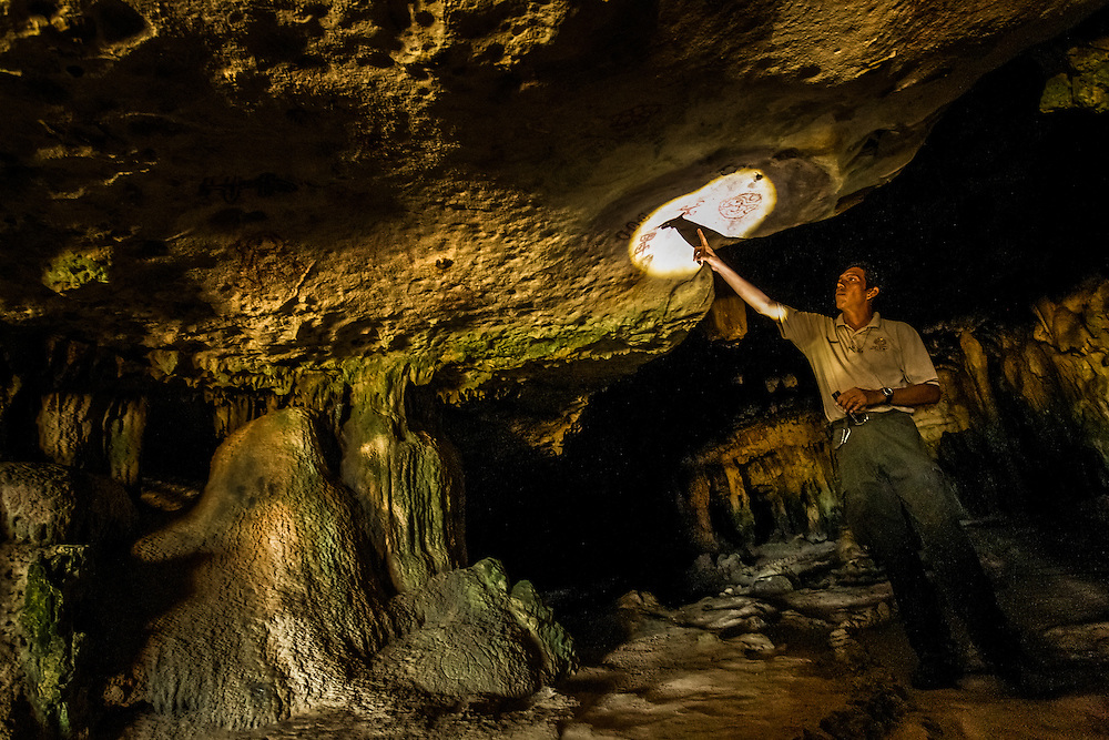 ARUBA - A park ranger shows brownish-red petroglyphs to a group of tourists as they explore Fontein Cave in Arikok National Park. The caves here were primarily used, as they were throughout the Caribbean, for religious and funeral rites, and as shelter against the forces of nature. PHOTO: Meridith Kohut for The New York Times