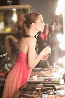 Woman stands in pink slip looking in dressing room mirror