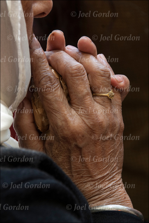 Close up of hands of Sikh-American elderly woman wearing sari or saree, praying and chanting before the start of the annual Sikh Day Parade in NYC.
