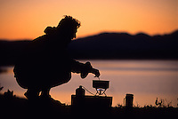A young man cooks breakfast on the shore of Jackson Lake in Grand Teton National Park, Wyoming.