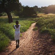 A girl is heading home in the dying light in rural Makurdi in Benue Sate, Nigeria.Benue state has got one of the highest HIV prevalence in Nigeria and EVA aim to target vulnerable children who would otherwise miss out of being tested for HIV and therefor not know their HIV statues. EVA runs a programme in the community called Window of Hope where children once a week meet to find support with each other and to receive psycho-social help. Many of the children are from HIV effected families and live precarious lives.  Education As a Vaccine Against Aids (EVA) in Nigeria.Education As a Vaccine Against Aids (EVA) in Nigeria.