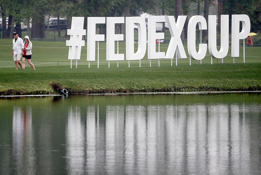 People walk by the FedExCup sign at the Shell Houston Open-Round 1 at the Golf Club of Houston on Wednesday, March 31, 2016 in Humble, TX. (Photo: Thomas B. Shea/For the Chronicle)