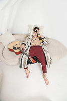 Young man with guitar drinking while lying on sofa